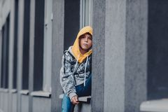 Pre-teen boy on a street in a big city next to a high-rise building alone. Portrait of a serious looking young boy in the city street Royalty Free Stock Images