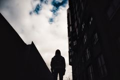 Pre-teen boy on a street in a big city next to a high-rise building alone. Lifestyle of a serious looking young boy in the city street close Royalty Free Stock Photography