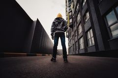 Pre-teen boy on a street in a big city next to a high-rise building alone. Lifestyle of a serious looking young boy in the city street Royalty Free Stock Images