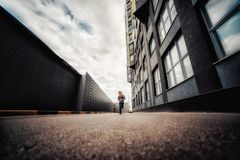 Pre-teen boy on a street in a big city next to a high-rise building alone. Lifestyle of a serious looking young boy in the city street. It runs on the road Stock Photos