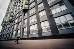 Pre-teen boy on a street in a big city next to a high-rise building alone. Lifestyle of a serious looking young boy in the city street. It runs on the road Royalty Free Stock Photography