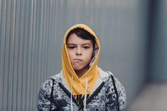Pre-teen boy on a street in a big city next to a high-rise building alone. Lifestyle of a serious looking young boy in the city street. portrait of a young boy Stock Photo