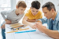 Pre-teen boys learning how to use compass. Easy lesson. Curious pre-teen boys leaning over their fathers work desk and learning how to use the compass while royalty free stock image