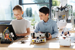 Pre-teen boys programming their robotic car Royalty Free Stock Image