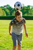 Pre-teen caucasian boy playing outside. Pre-teen boy playing football in a park stock photography