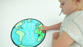 Girl colouring in a map of the world. Pre teen caucasian girl colouring in a map of the world stock footage
