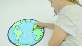 Girl colouring in a map of the world. Pre teen caucasian girl colouring in a map of the world stock video