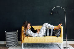 Pre teen child on the couch against black wall in modern living. Home portrait of pre teen child girl wearing pajama hugging her cat on the yellow couch against Stock Photo