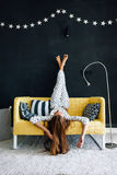 Pre teen child on the couch against black wall in modern living. Home portrait of pre teen child girl wearing pajama relaxing and chilling on the yellow couch Royalty Free Stock Photo