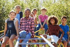 Pre-teen friends sitting on climbing frame in playground Royalty Free Stock Photos