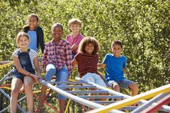 Pre-teen friends sitting on climbing frame in playground Stock Image
