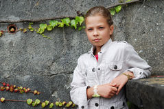 Pre-teen girl against the stone wall. Royalty Free Stock Image