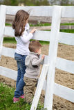 Pre-teen girl and Baby boy on the a white picket fence beside th. E horse Stock Photography