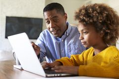 Pre teen girl African American  girl using a laptop computer sitting at table in the dining room with her home tutor, close up, se. Pre teen girl black girl royalty free stock photography