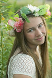 A pre-teen girl with long brown hair with wreath in meadow. Royalty Free Stock Image