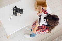 Pre-teen girl showing how to use VR headset correctly. Helping the inexperienced. The top view of a petite pre-teen girl showing how to use a VR headset Stock Image