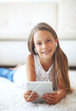 Pre teen girl with tablet pc. Pre teen girl playing on tablet pc laying down on a white carpet at home Stock Photo