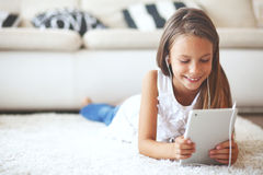 Pre teen girl with tablet pc. Pre teen girl playing on tablet pc laying down on a white carpet at home Stock Photography