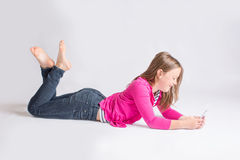 Pre-teen girl using cellphone. Young girl lying on belly laughing while using her cell phone Royalty Free Stock Image