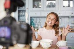 Pre-teen girl video blogging in the kitchen waving her hands stock photo