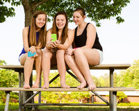 Pre-teen girls texting while hanging out in front  Stock Photos