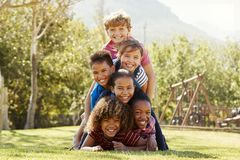 Pre-teen school friends lying a pile in a park Royalty Free Stock Images