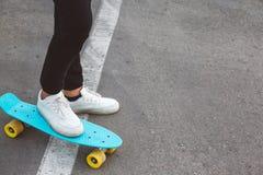 Pre teen skater on the city street. Girl wearing fashion sportswear rollerskating on skateboard in the city street, urban hipster style, feet in shoes closeup Stock Photo