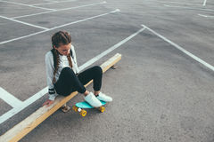 Pre teen skater on the city street. 11-12 years old tween girl wearing fashion sportswear rollerskating on skateboard in the city street, urban hipster style Royalty Free Stock Image