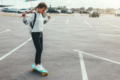 Pre teen skater on the city street. 11-12 years old tween girl wearing fashion sportswear rollerskating on skateboard in the city street, urban hipster style Royalty Free Stock Images