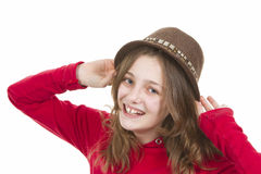 Pre teen girl smiling and putting on her hat Royalty Free Stock Image