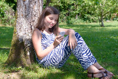 Pre teenager girl texting on mobile phone Royalty Free Stock Photography