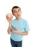 Pre tienerjongen die een spaarpot rammelt stock fotografie