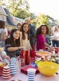 Pre-tienermeisjes die aan camera bij een het voedsellijst van de blokpartij glimlachen royalty-vrije stock foto's