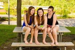 Pre-tienermeisjes die terwijl het hangen uit vooraan texting  Stock Foto's