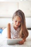 Pre tonårig flicka med minnestavlaPC Royaltyfria Bilder