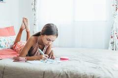 Pre tonårig flicka som gör skolaläxa Arkivbild