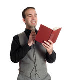 Preacher. A young preacher is reading something out of a book into a microphone, isolated against a white background royalty free stock photography