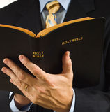 Preacher with Bible. A man is business suit reading the Bible could be a preacher royalty free stock photography