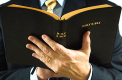Preacher with Bible. A man is business suit reading the Bible could be a preacher stock photography