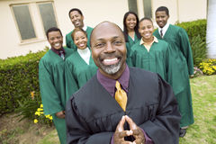 Preacher And Choir Standing In Front Of Church. Portrait of confident preacher and choir standing in front of church stock image