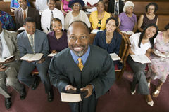 Preacher Holding Bible With Congregation Sitting In Church. Portrait of confident preacher holding Bible with congregation sitting in church royalty free stock image
