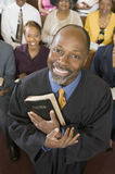 Preacher Holding Holy Bible With Congregation Sitting In Church Royalty Free Stock Photos