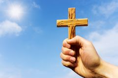 Preacher holding wooden cross against blue sky Royalty Free Stock Photography