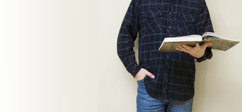 Preacher man. Torso of a preacher man holding a big book, reading. Space for text at the left stock image