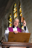 Preacher on pulpit. Mature preacher on wooden pulpit during mass royalty free stock image