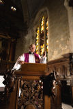 Preaching on a pulpit. Roman catholic priest preaching on an antique 17th century pulpit in a medieval church Royalty Free Stock Image