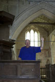 Preaching to the Choir. Man raising his hand while preaching at old church alter Royalty Free Stock Image