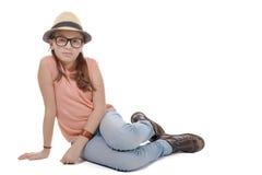 Preadolescente en los vaqueros, las botas, el sombrero y la camiseta sentándose en el piso Foto de archivo libre de regalías