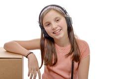 Preadolescente que escucha la música con los auriculares en blanco Foto de archivo libre de regalías