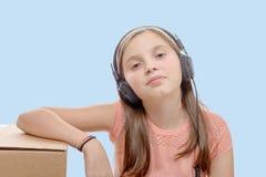Preadolescente que escucha la música con los auriculares, fondo azul Imágenes de archivo libres de regalías